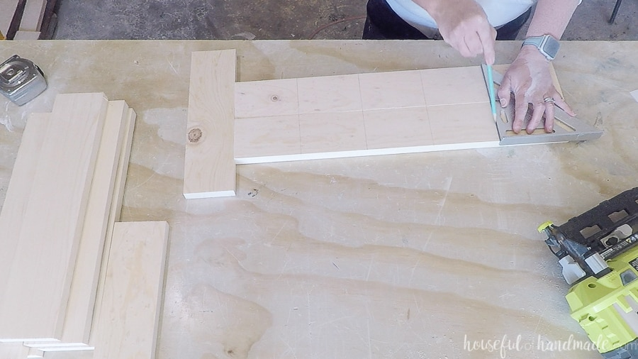 Marking the placement of the shelves with a speed square and pencil on the boards.