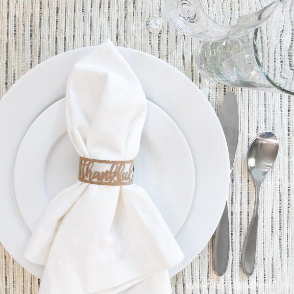 Paper Thanksgiving napkin ring around a white napkin on a place setting.
