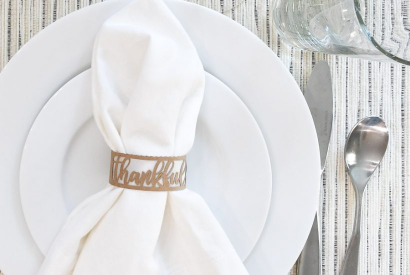 Paper Thanksgiving napkin ring around a white napkin on a place setting.