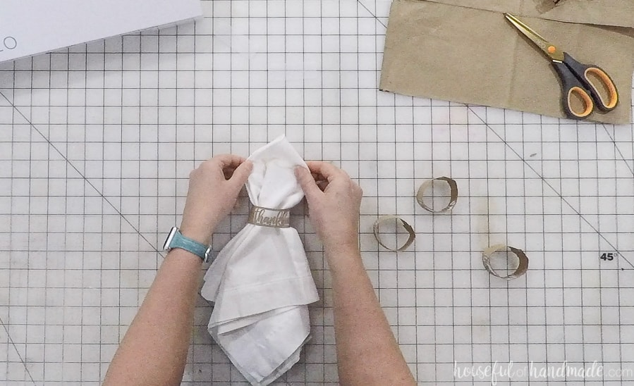 Sliding a white napkin into the DIY thanksgiving napkin ring.
