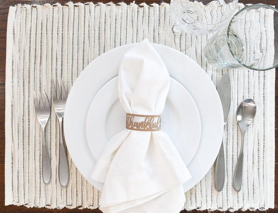 Table setting on a natural colored placemat with a white napkin with a brown paper napkin ring with word thankful on it.