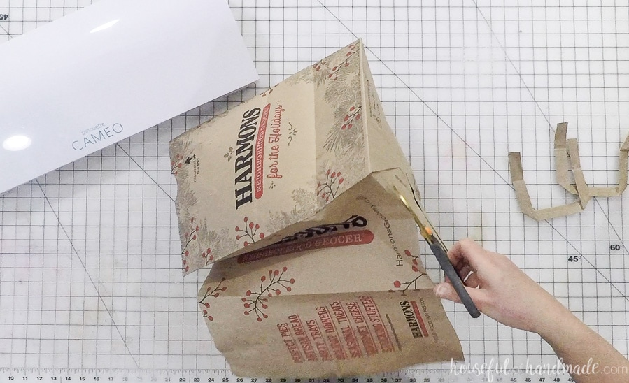 Cutting open the grocery bag to make paper napkin rings.