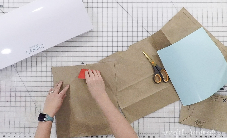 Putting the brown paper on a Silhouette cutting mat.
