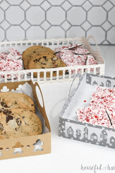 Three DIY paper trays with Christmas designs on them filled with treats.
