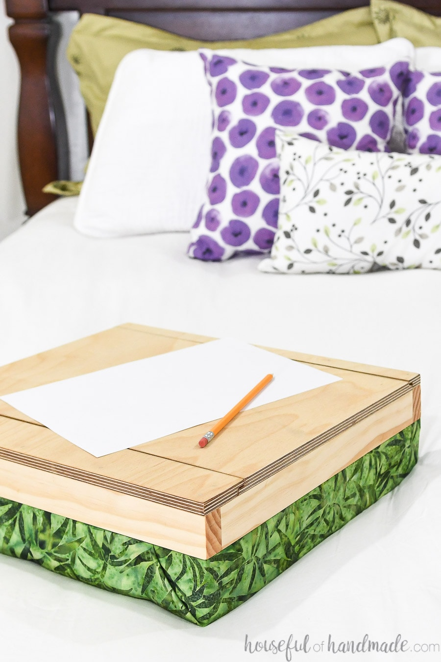 DIY lap desk with cushion covered in green leaf print on a bed.