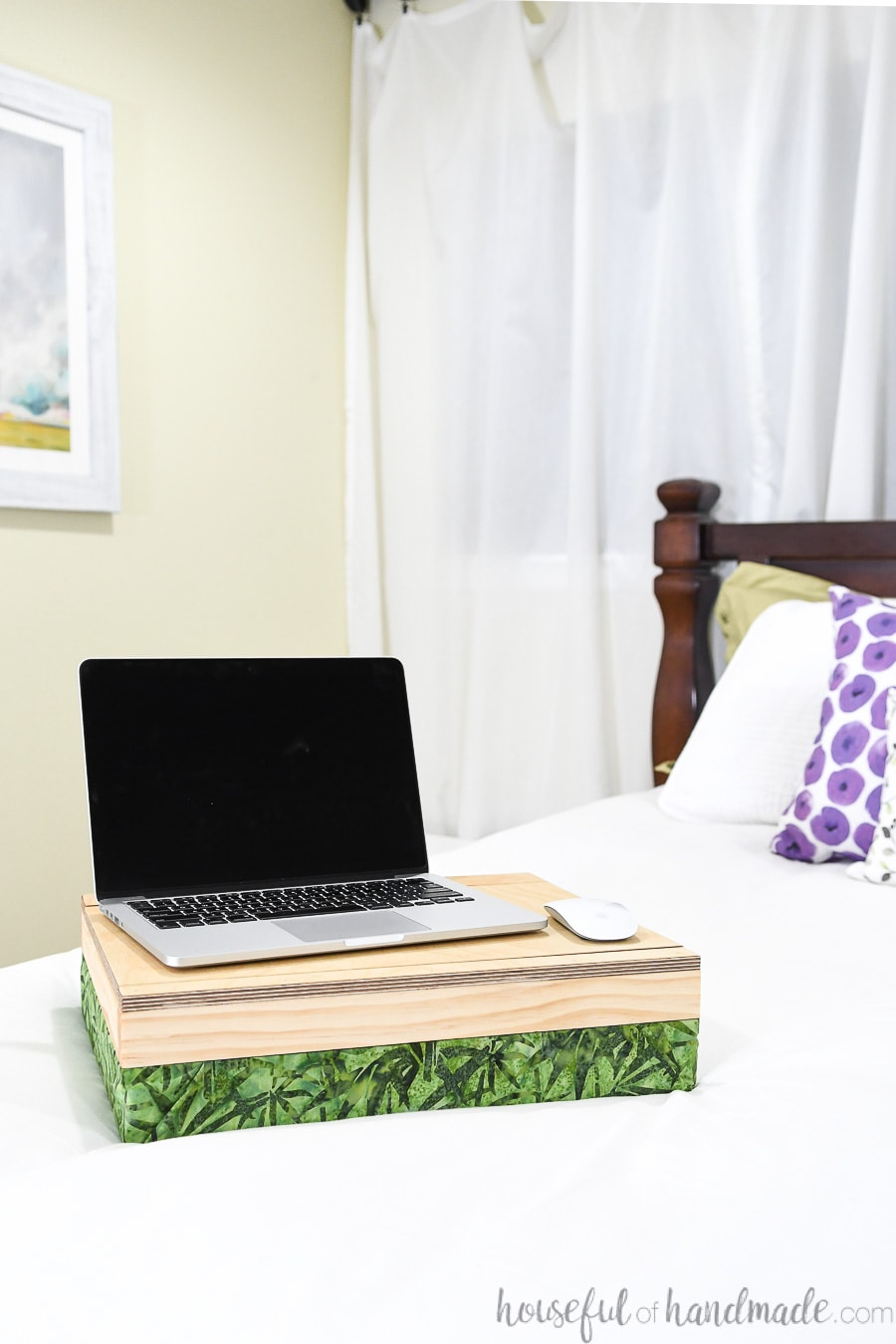 Easy DIY lap desk with a laptop and mouse on it, sitting on a bed.