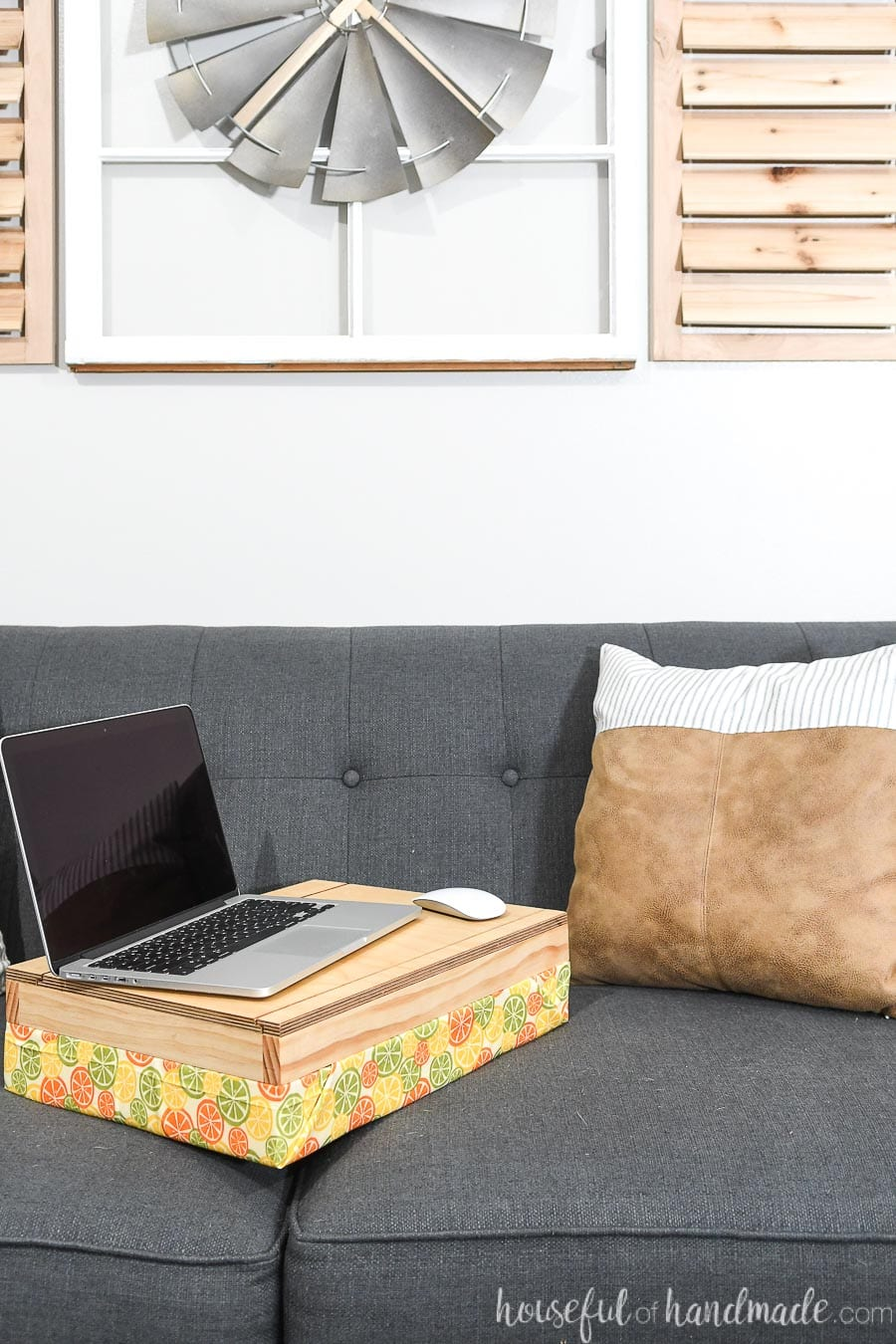 Homemade lap desk with storage on the couch with a laptop on it.
