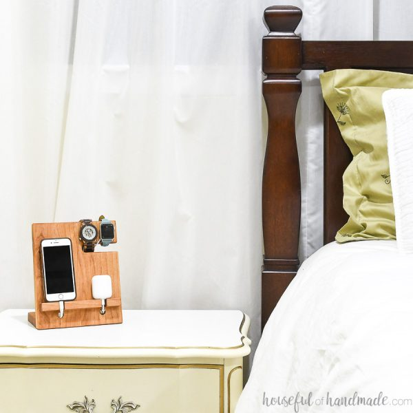 Wood valet holding phone, watch and bluetooth earbuds while charging next to the bed.