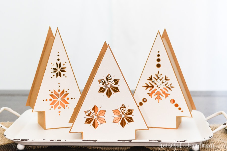 Three Nordic Christmas tree lanterns on a tray made out of paper.