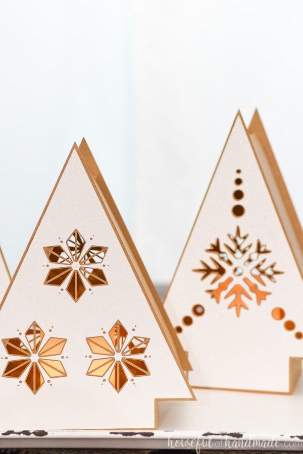Close-up photo of 2 of the Christmas tree shaped paper lanterns with Nordic designs on them.
