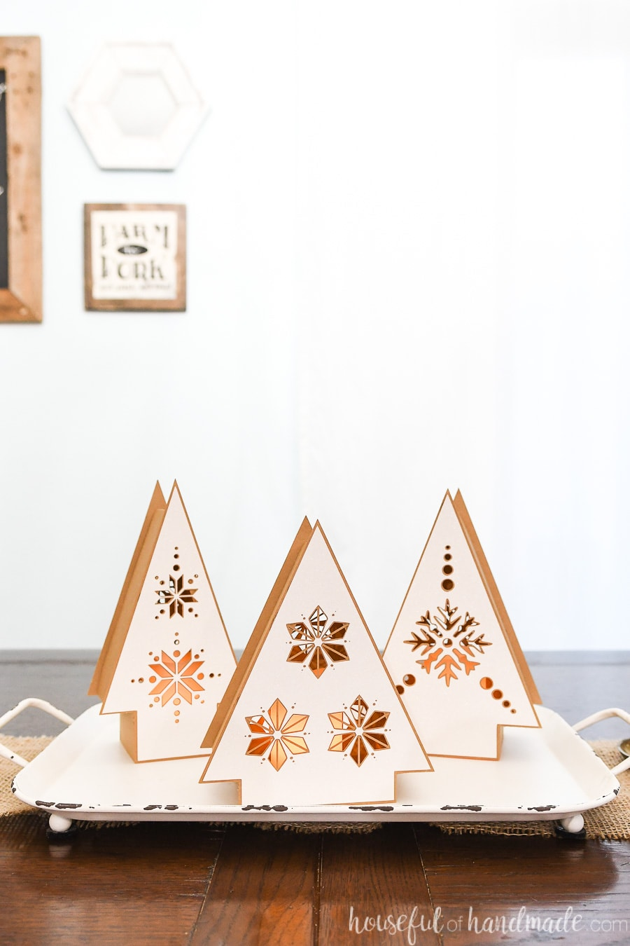 Christmas table centerpiece made of 3 Nordic paper Christmas tree shaped lanterns on a tray.
