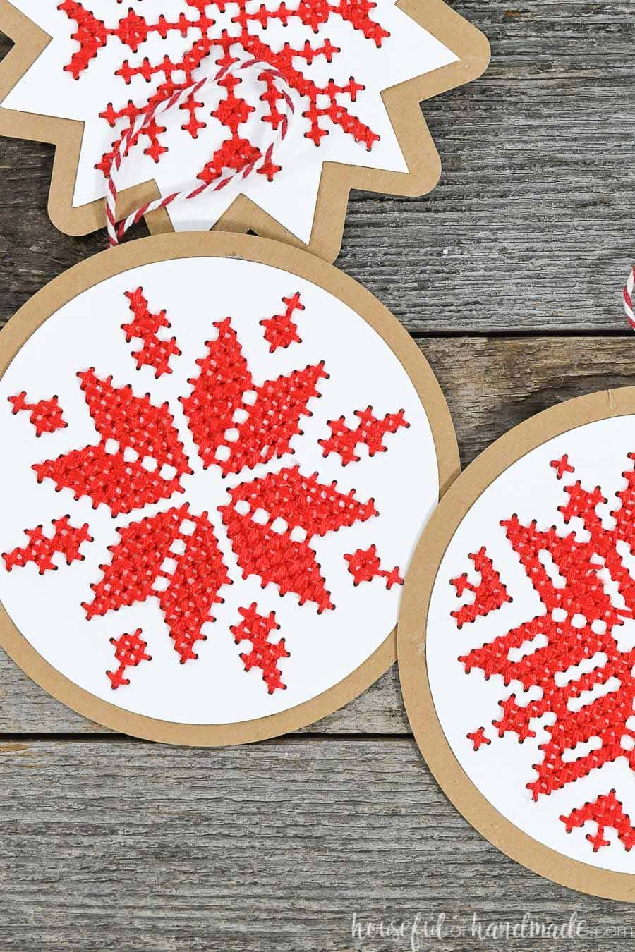 Cross-stitched snowflake designs on paper Christmas ornaments laying on a wood background.
