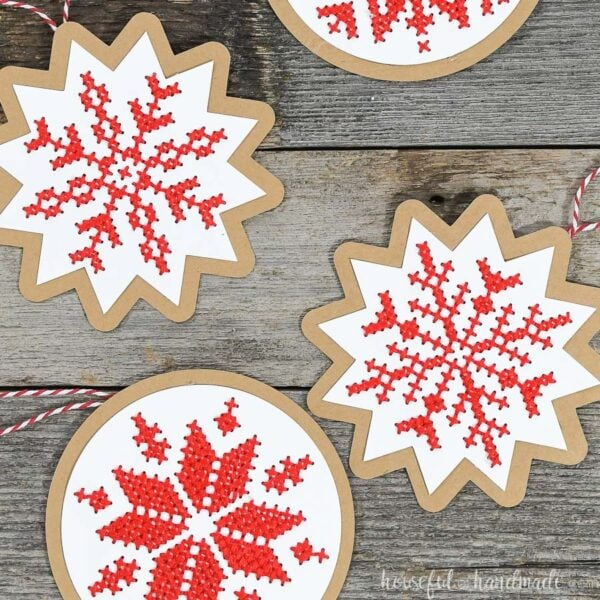 Close up of 4 Scandinavian red and white cross-stitched Christmas ornaments.