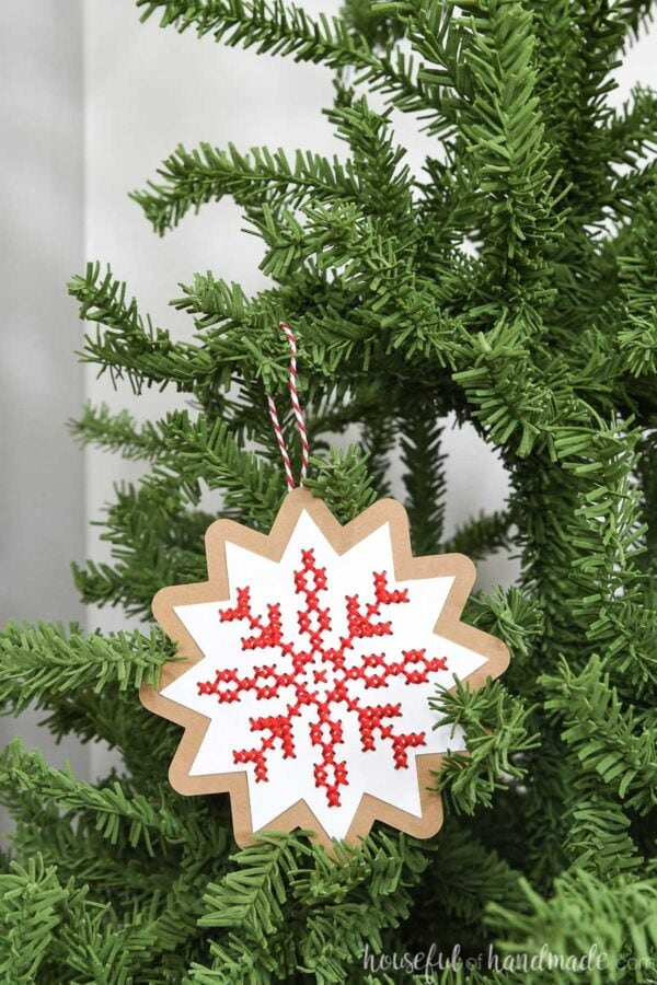 Snowflake design on a paper Christmas ornament hanging on a tree.