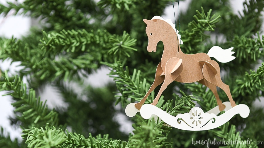 One paper Christmas ornament on a tree that looks like a vintage rocking horse.