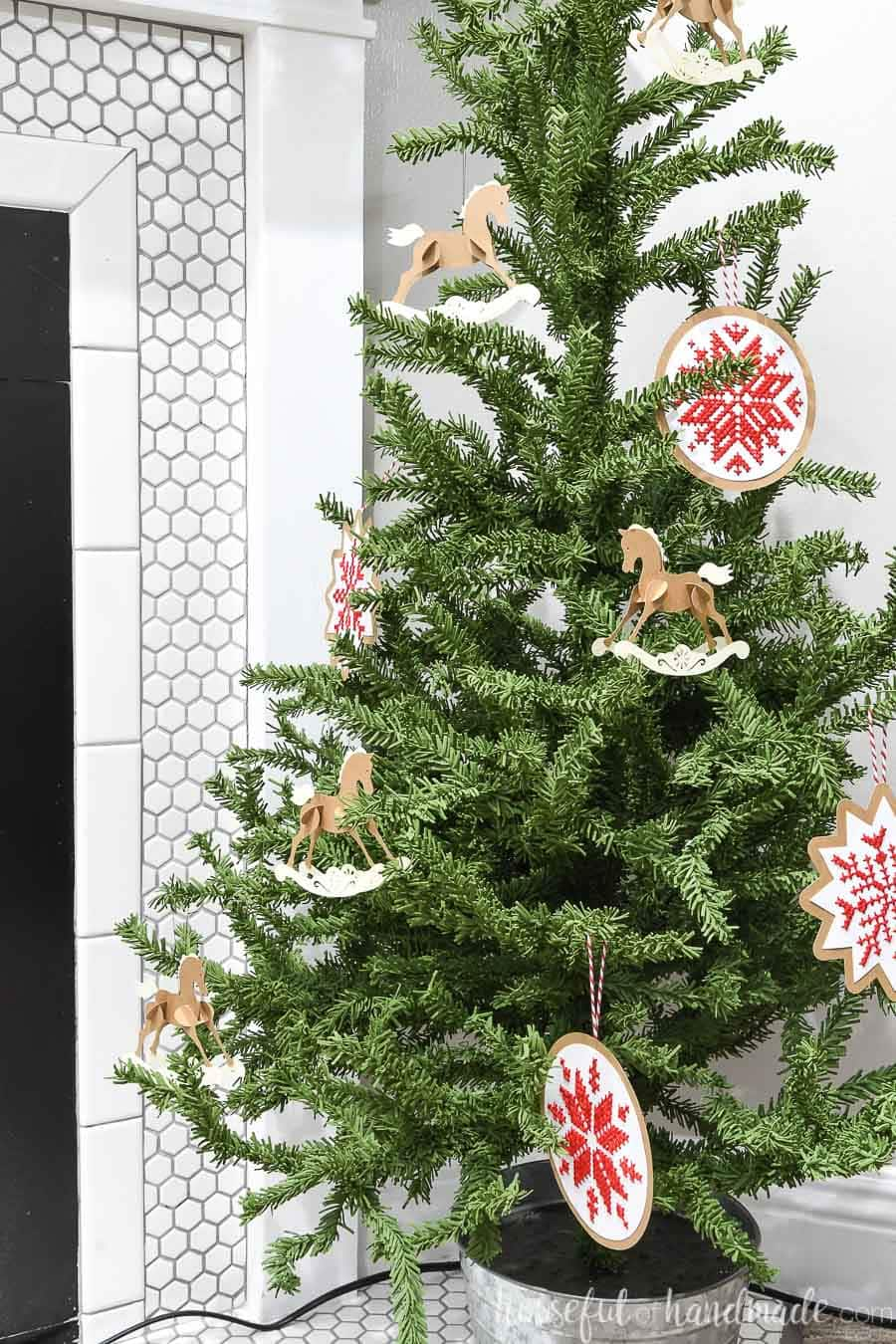 Mini Christmas tree decorated with paper rocking horse ornaments and cross-stitch Nordic snowflakes.