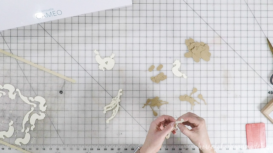 Pieces of the paper rocking horse ornaments on a work table.