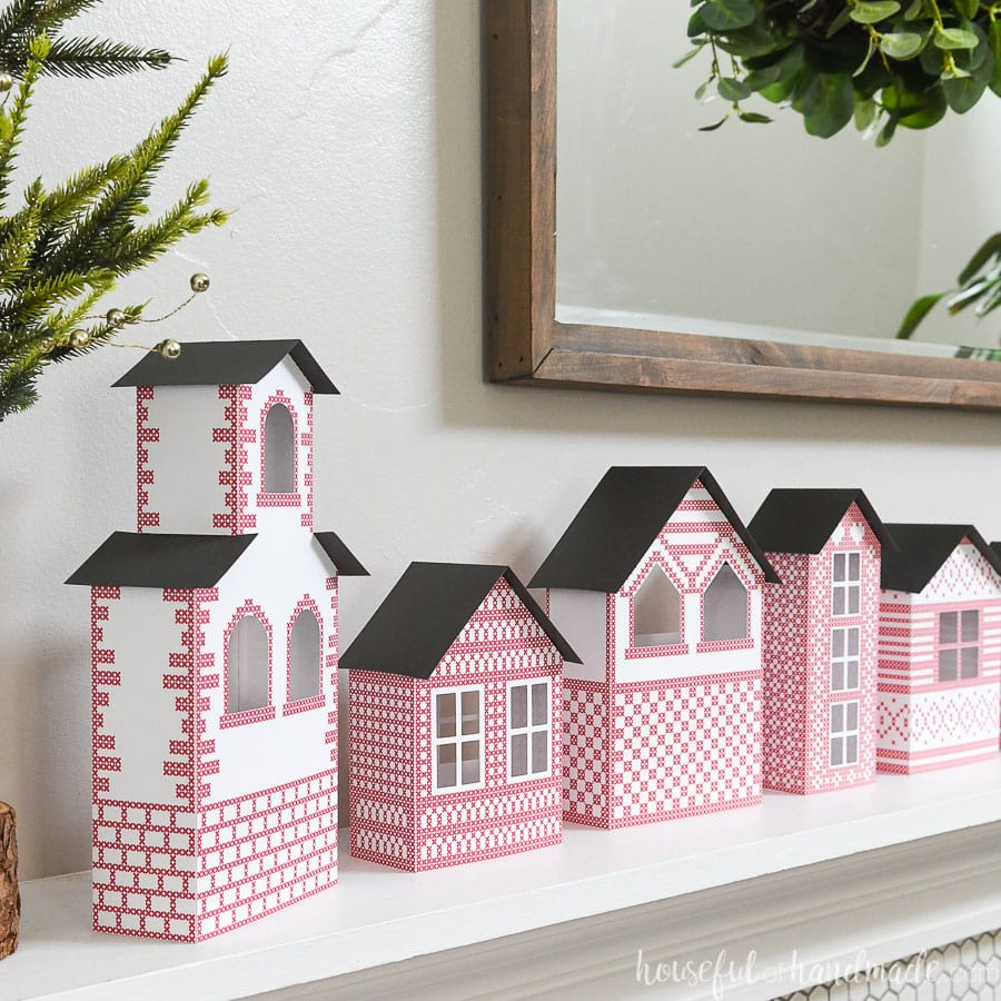 Closeup view of 5 paper houses making a Christmas village above the fireplace.