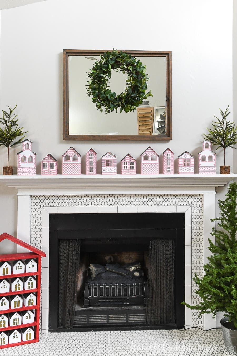 Fireplace and mantel decorated for Christmas with an advent calendar and small tree on the hearth and DIY paper Christmas village on the mantel.