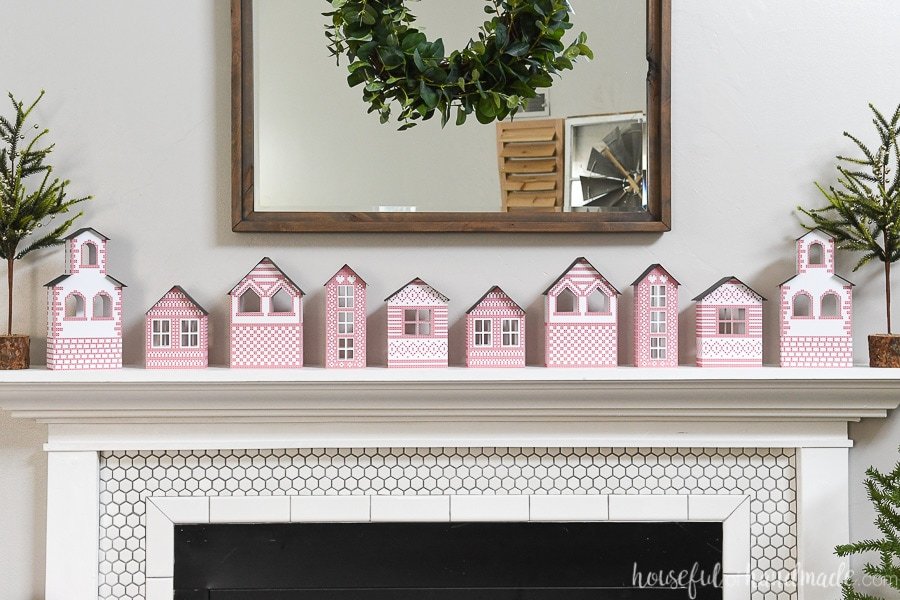 Ten paper Christmas houses with Scandinavian inspired cross-stitch design on them on a mantel.
