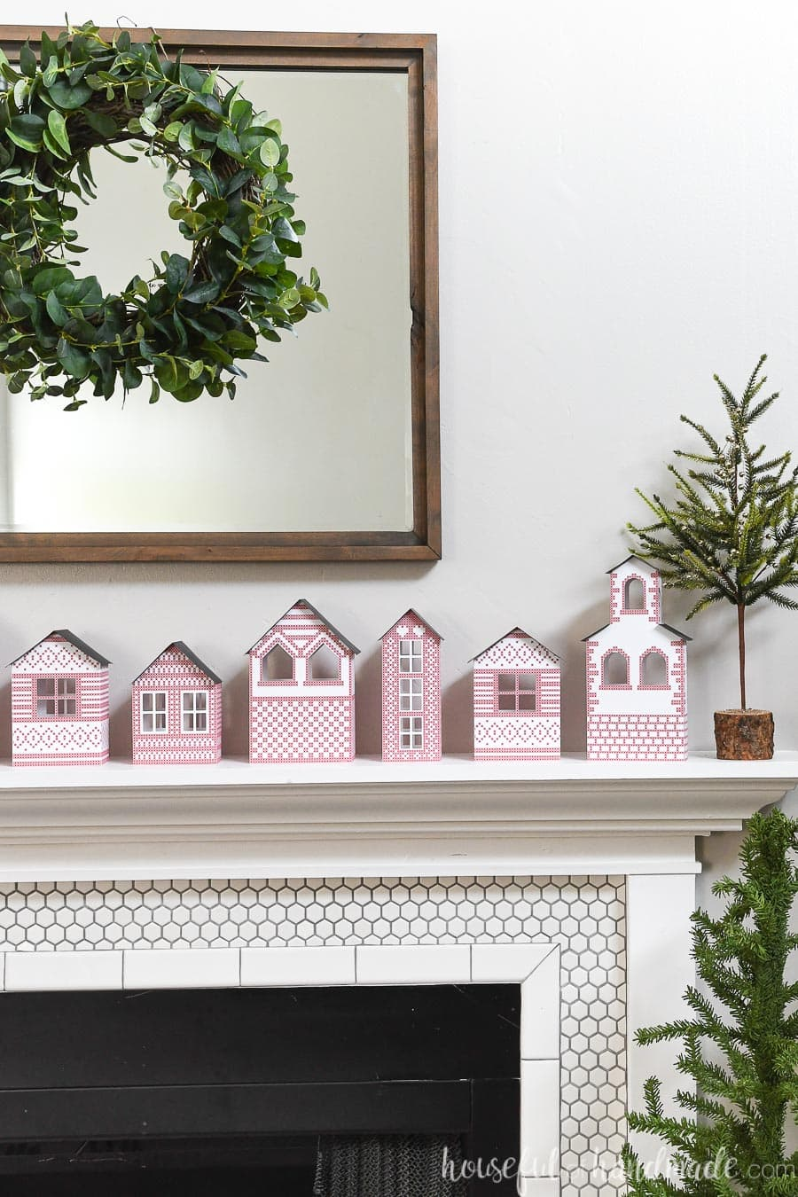 Five different designs on paper Christmas houses sitting on the mantle.