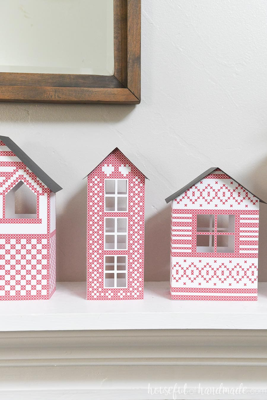 Paper Christmas village with Scandinavian inspired house designs with cross-stitched patterns on them.