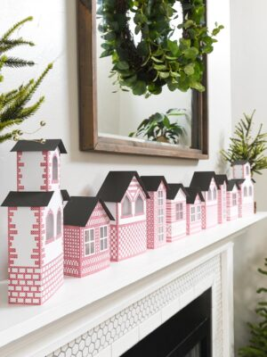 Fireplace decorated with an easy to make DIY Christmas village from paper.