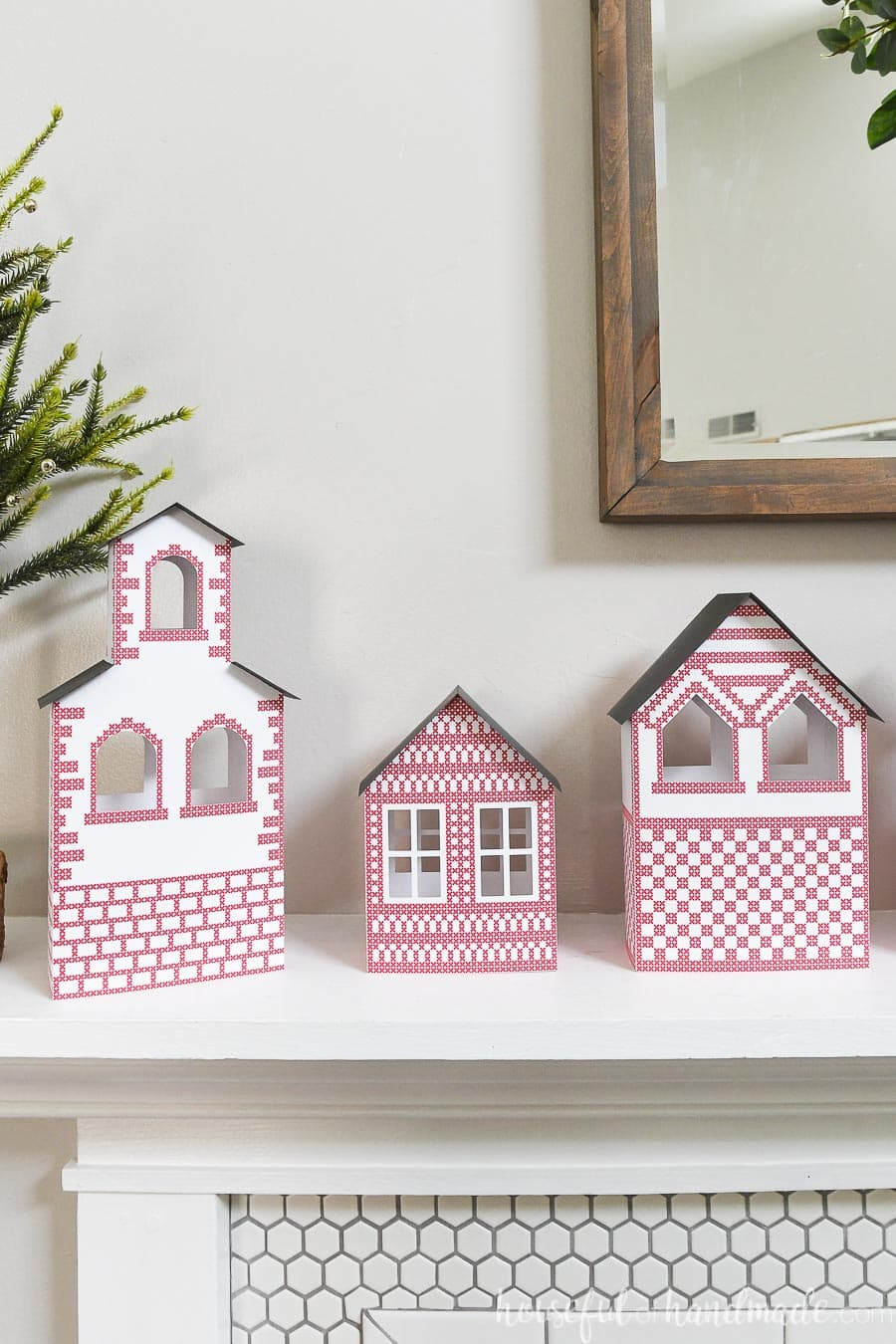 Three paper Christmas houses with red details, including a simple church.