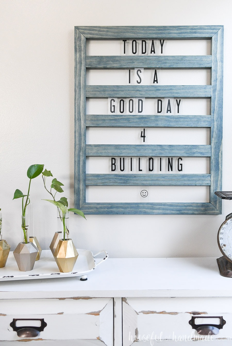 Worn navy stained wood sliding letter board hanging on the wall above a console table.