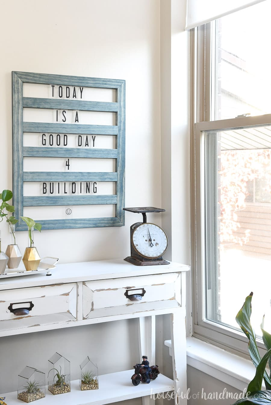 Corner of a room overlooking the window with a farmhouse console table decorated with a DIY letter board above it.