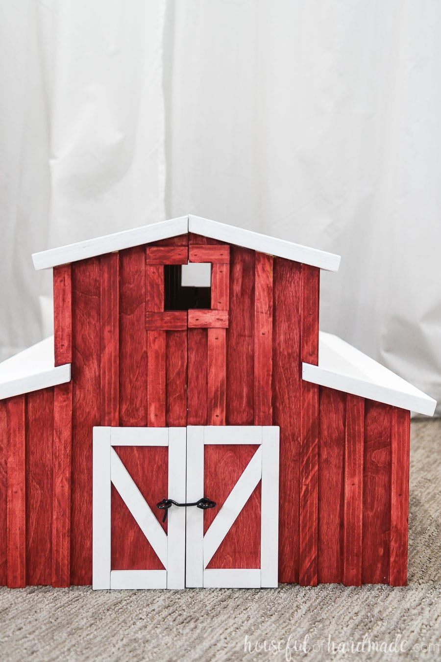 Front view of the toy barn build with lots of details and white trimmed barn doors.