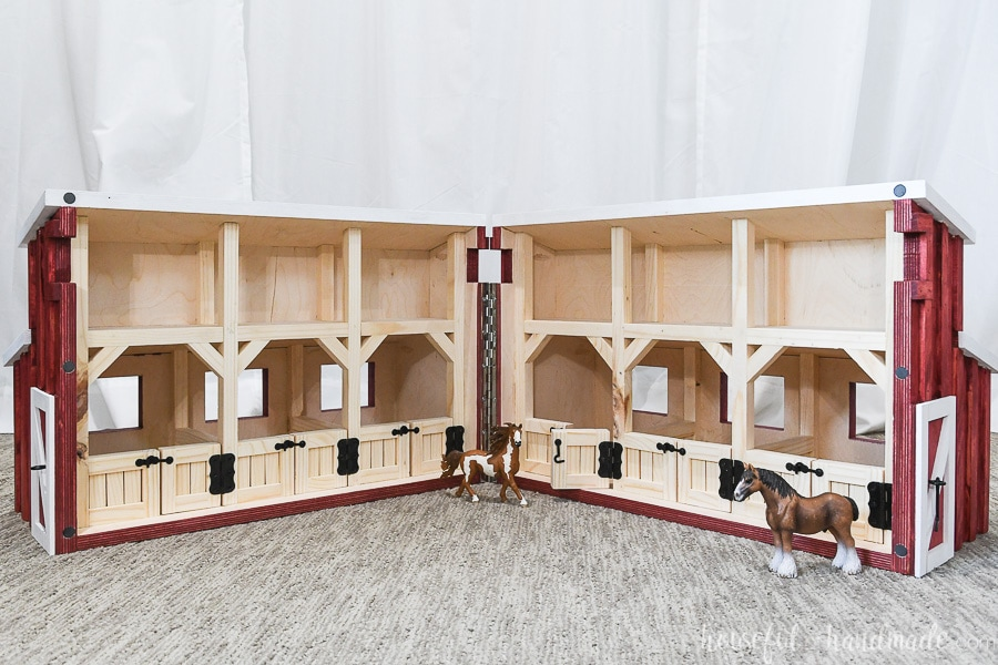 Wooden toy barn opened up to expose 6 horse stalls and loft area.
