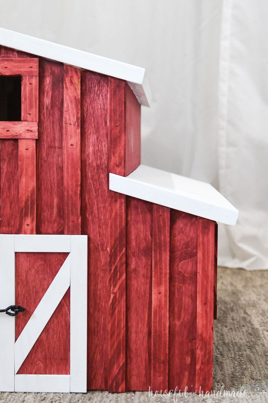 Front view of 1/2 of the wooden toy barn with red stain and white trim.