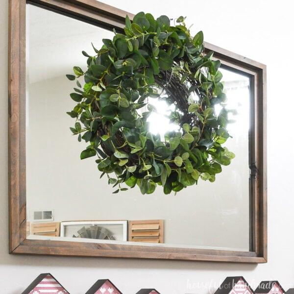 Easy DIY eucalyptus wreath hanging over a mirror above the mantel.