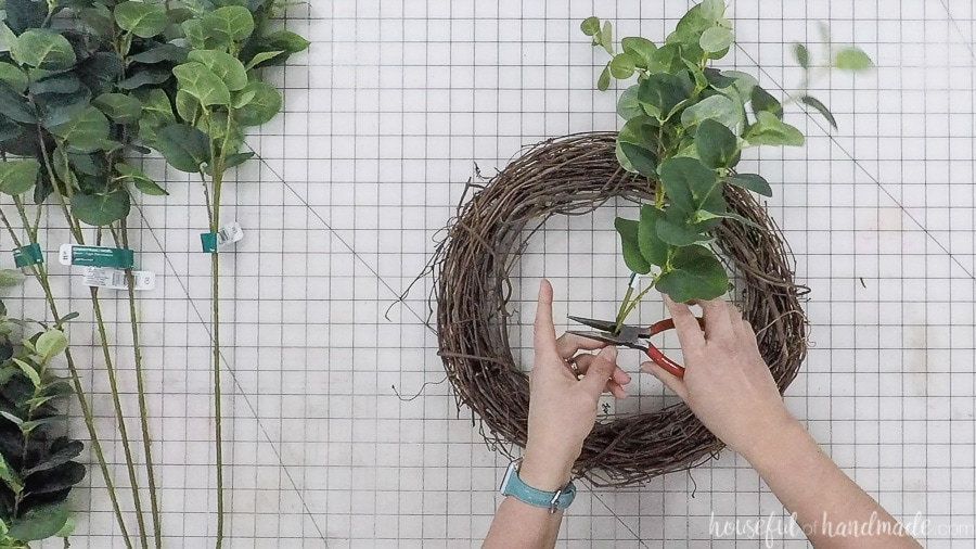 Cutting faux eucalyptus stems with wire cutters.