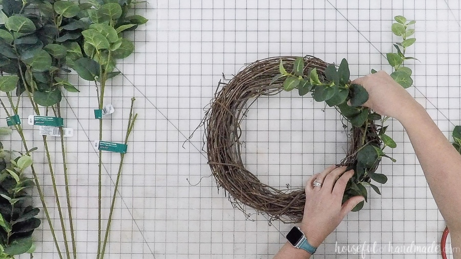 Inserting the eucalyptus springs into grapevine wreath form.