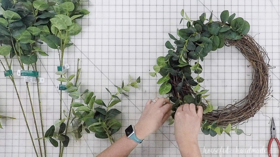 Adding more stems to the diy eucalyptus wreath.