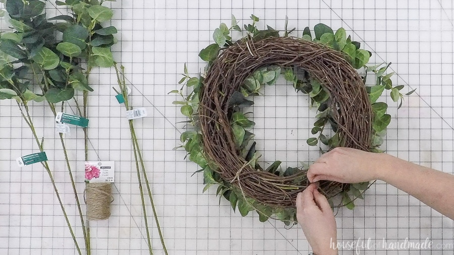 Tying twine to the top of the wreath to hang it easily.