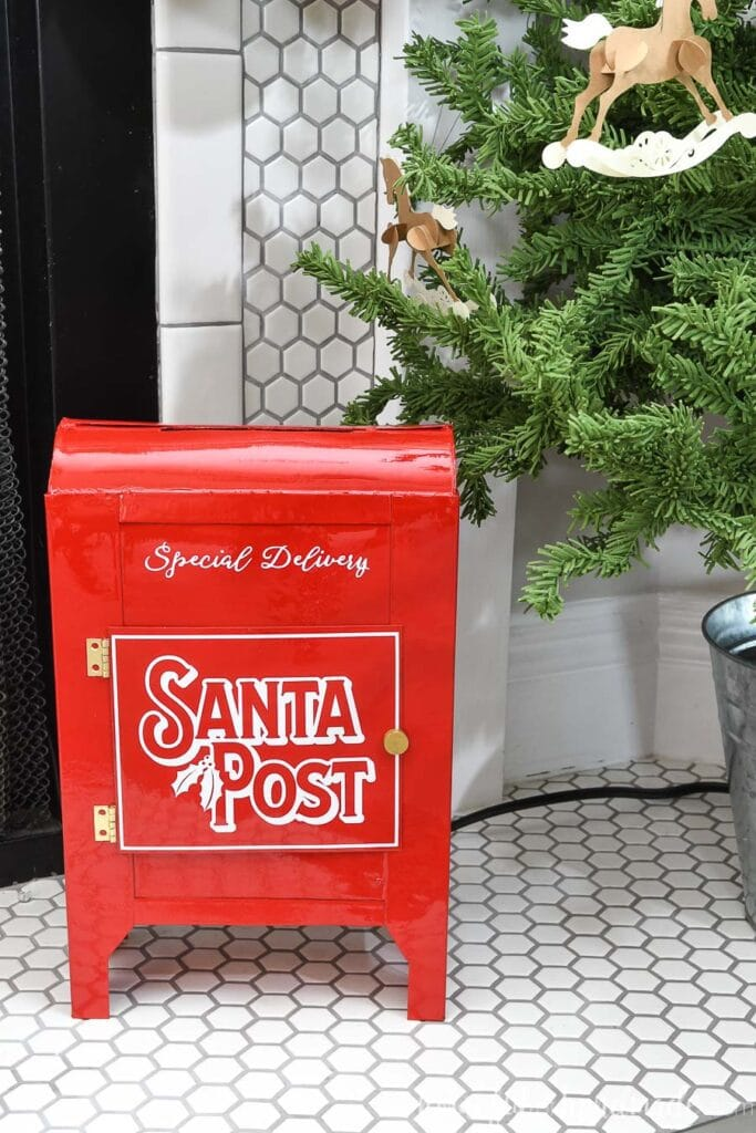 DIY Santa Mailbox made from empty cereal boxes sitting on the fireplace hearth.