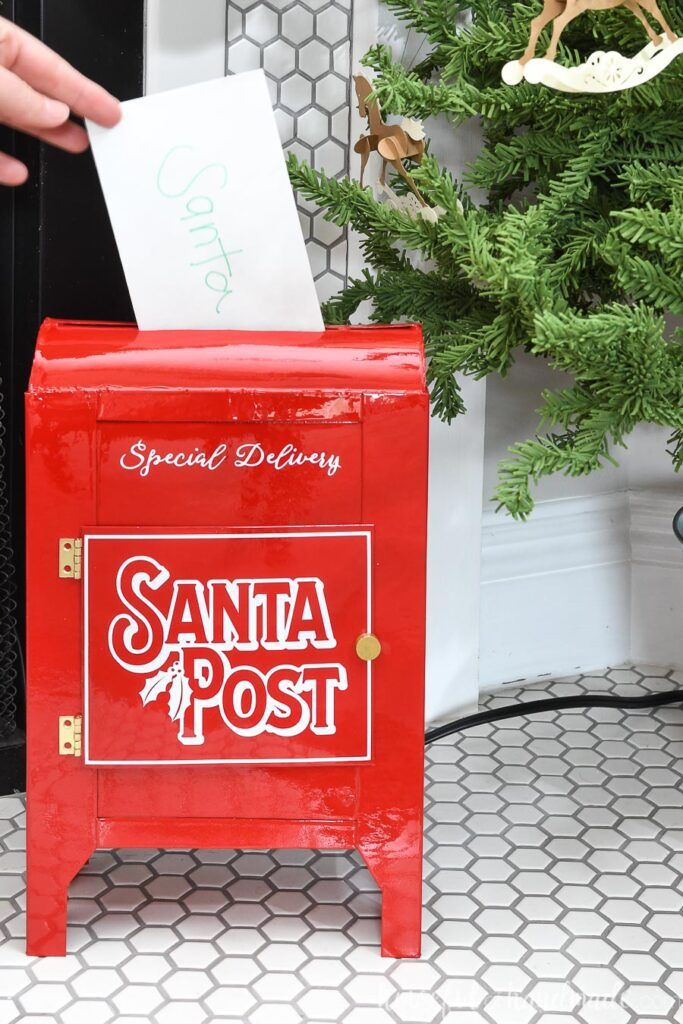 Shiny red Santa mailbox with letter being slid in the top.