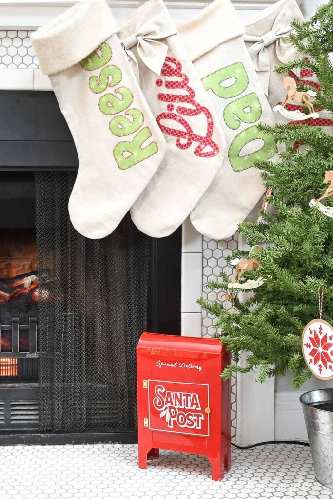 Fireplace hearth decorated with small tree, personalized stockings and red DIY Santa mailbox.