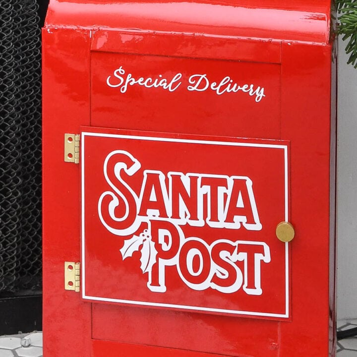 Close-up of the shiny red DIY Santa's mailbox with vinyl Santa Post design on the door.