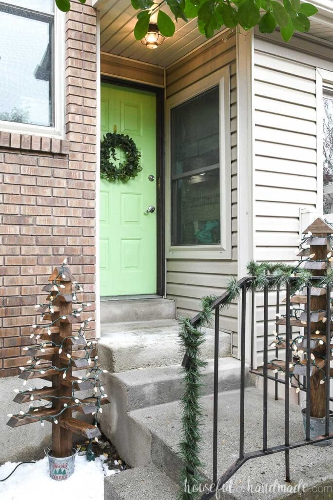 Entryway decorated for Christmas with DIY outdoor Christmas trees with lights on them around the porch.