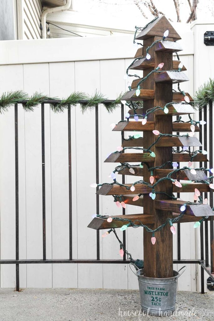 Outdoor Christmas tree with lights on the porch by a railing wrapped in garland.