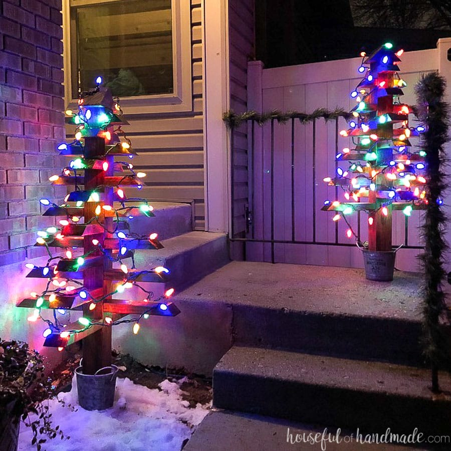 Two 2x4 Christmas trees with colored Christmas lights on the porch at night.
