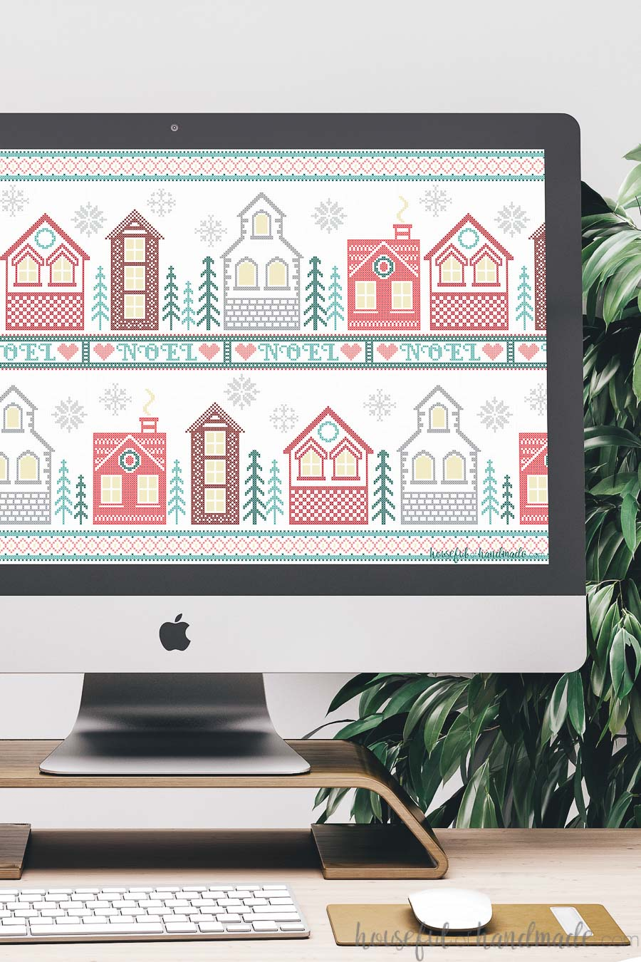 iMac computer with a cross-stitch Christmas village digital wallpaper on the screen.