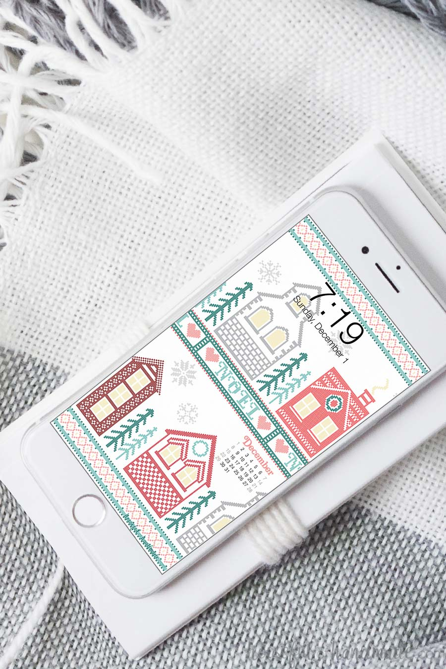 White iPhone showing the Christmas cross-stitch village design on the background.