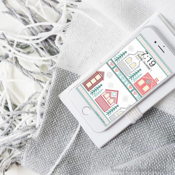 White smartphone on a blanket with the free digital wallpaper for December on the screen.