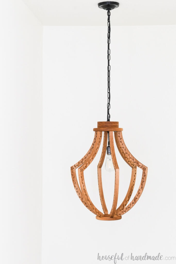 Large wood light fixture with black chain hanging from the ceiling.