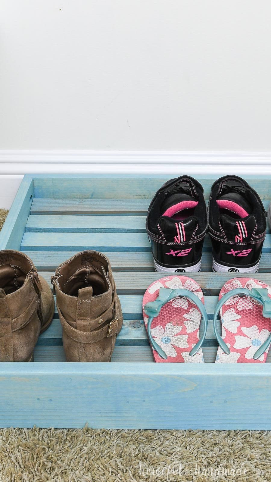 Close up view of the easy to build shoe organizer tray on the floor of the closet with shoes in it.